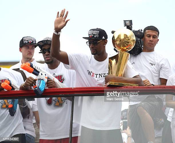 Forward Chris Bosh of the Miami Heat holds the Larry O'Brien NBA Championship Trophy as he rides a bus during the championship victory parade on June...