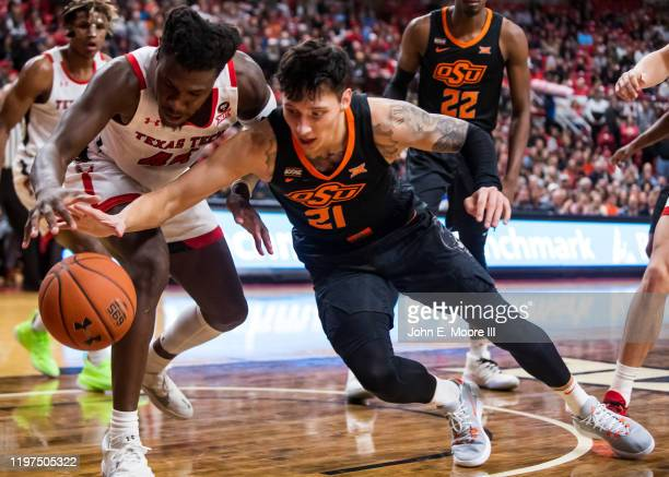 Forward Chris Clarke of the Texas Tech Red Raiders and guard Lindy Waters III of the Oklahoma State Cowboys battle for the ball during the first half...