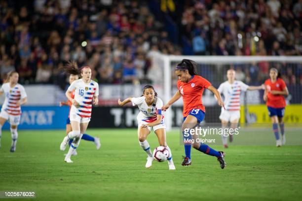 Forward Christen Press of the US Women's National team goes for the ball against Defender Fernanda Pinilla of Chile during the friendly match against...