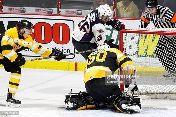 Forward Cole Purboo of the Windsor Spitfires slips the puck past goaltender goaltender Jeremy Helvig of the Kingston Frontenacs on October 20 2016 at...