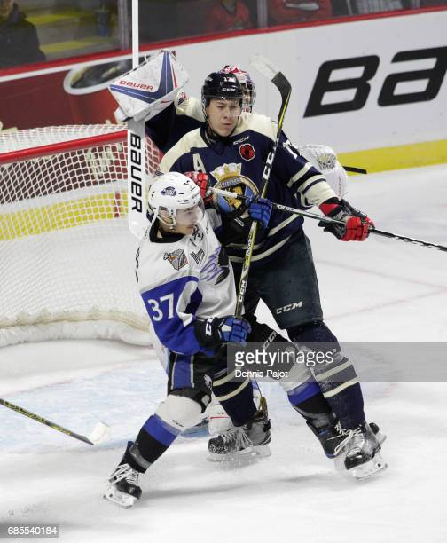 Forward Cole Reginato of the Saint John Sea Dogs battles in front of the net against defenceman Logan Stanley of the Windsor Spitfires on May 19 2017...