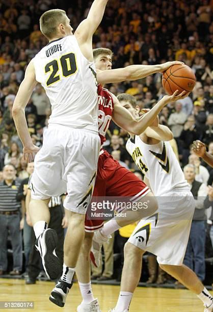 Forward Collin Hartman of the Indiana Hoosiers goes to the basket between forward Jarrod Uthoff and center Adam Woodbury of the Iowa Hawkeye in the...