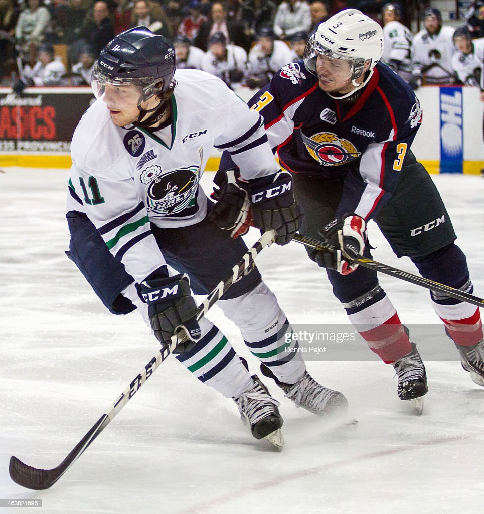 Forward Connor Chatham #11 of the Plymouth Whalers skates against defenceman Liam Murray #3 of the Windsor Spitfires on February 18, 2015 at the WFCU Centre in Windsor, Ontario, Canada.