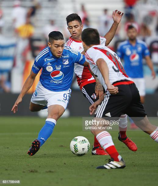 Forward Cristian Daniel Arango of Colombian team Millonarios FC tries to get past midfielder Gonzalo Martinezand defender Luis Olivera of Argentine...