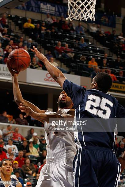 Forward Damian Johnson of the Minnesota Golden Gophers attempts a shot against forward Jeff Brooks of the Penn State Nittany Lion in the first round...