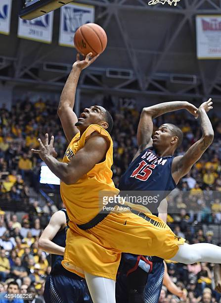 Forward Darius Carter Jr #12 of the Wichita State Shockers drives and scores pas guard Reggie Baker of the Newman Jets during the first half on...