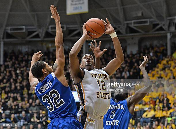 Forward Darius Carter of the Wichita State Shockers scores between defenders Manny Arop and Khristian Smith of the Indiana State Sycamores during the...
