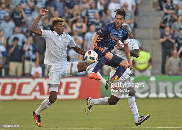 Forward David Villa of the New York City FC battles for the ball against defender Saad AbdulSalaam of Sporting Kansas City during the first half on...