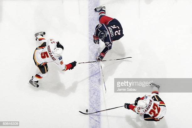 Forward Daymond Langkow of the Calgary Flames skates with the puck as defenseman Mark Giordano of the Flames defends against Jason Chimera of the...