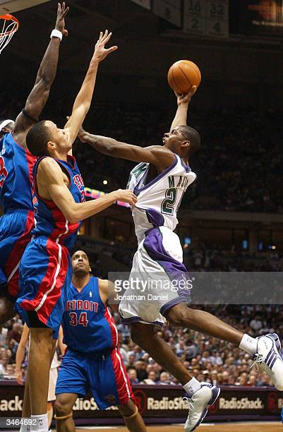 Forward Desmond Mason of the Milwaukee Bucks puts up a shot against center Ben Wallace and forward Tayshaun Prince of the Detroit Pistons during game...