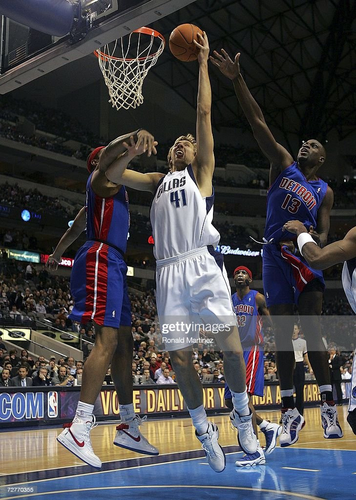 Forward Dirk Nowitzki #41 of the Dallas Mavericks drives the hoop against Rasheed Wallace #36 and Nazr Mohammed #13 of the Detroit Pistons at the American Airlines Center on December 7, 2006 in Dallas, Texas.