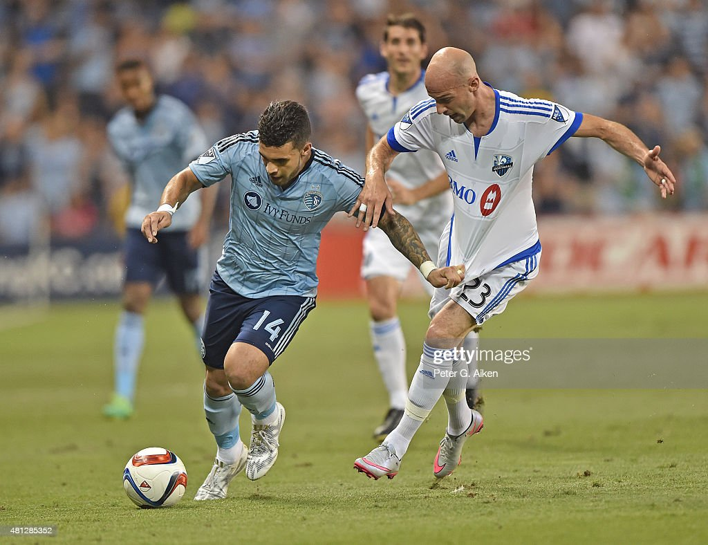 Forward Dom Dwyer #14 of Sporting Kansas City dribbles the ball against defender Laurent Ciman #23 of the Montreal Impact during the second half on July 18, 2015 at Sporting Park in Kansas City, Kansas.
