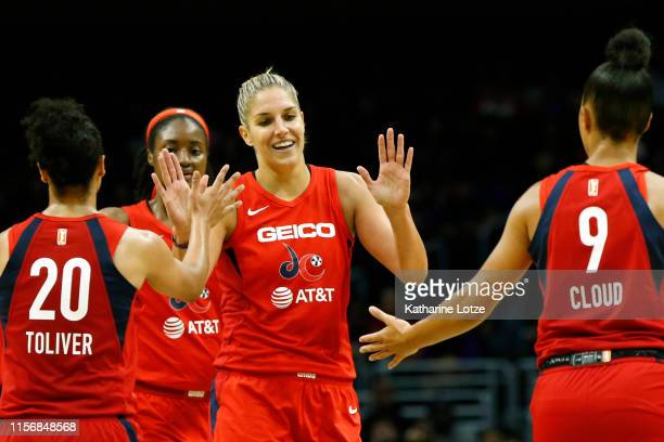 Forward Elena Delle Donne of the Washington Mystics highfives teammates guard Kristi Toliver and guard Natasha Cloud during a game against the Los...