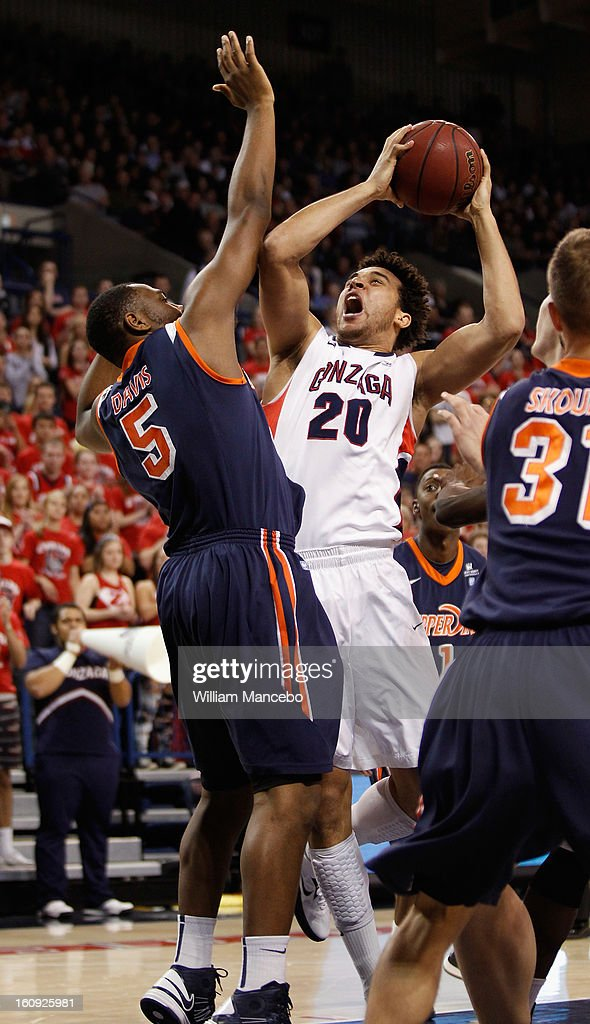 Forward Elias Harris #20 of the Gonzaga Bulldogs drives toward the basket while forward Stacy Davis #5 and guard Nikolas Skouen #31 of the Pepperdine Waves defend during the first half of the game at McCarthey Athletic Center on February 7, 2013 in Spokane, Washington.