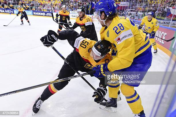 Forward Elias Lindholm of Sweden and forward Patrick Hager of Germany vie for the puck during the group A preliminary round match Sweden vs Germany...