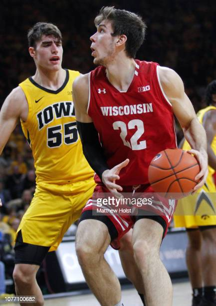 Forward Ethan Happ of the Wisconsin Badgers goes to the basket in the first half against guard Jordan Bohannon and forward Luka Garza of the Iowa...