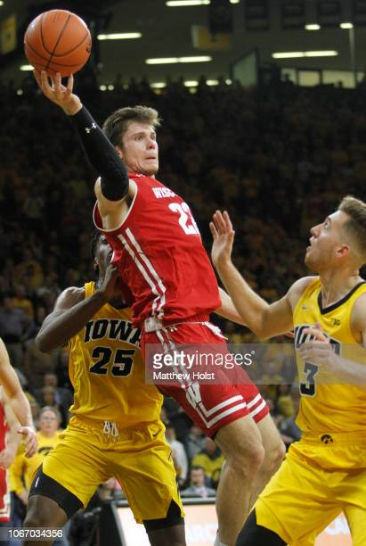 Forward Ethan Happ of the Wisconsin Badgers passes the ball away in the first half between guard Jordan Bohannon and forward Tyler Cook of the Iowa...
