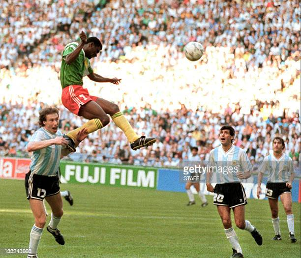 Forward Francois OmamBiyick from Cameroon scores on a header as Argentinian defenders Nestor Lorenzo and Juan Simon look on 08 June 1990 in Milan...