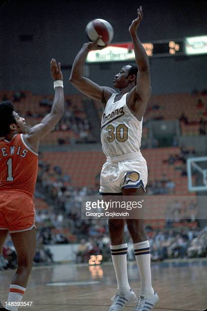 Forward George McGinnis of the Indiana Pacers shoots over guard Freddie Lewis of the Spirits of St Louis during an American Basketball Association...