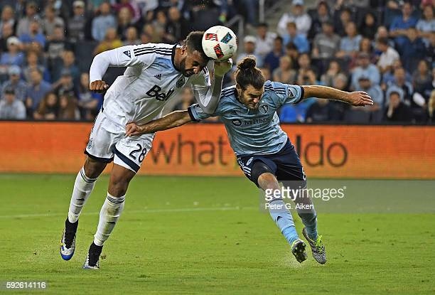 Forward Giles Barnes of the Vancouver Whitecaps FC heads a shot on goal against midfielder Graham Zusi of Sporting Kansas City during the first half...