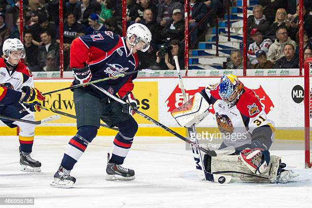 Forward Hayden McCool of the Windsor Spitfires moves the puck against goaltender Devin Williams of the Erie Otters on March 19 2015 at the WFCU...