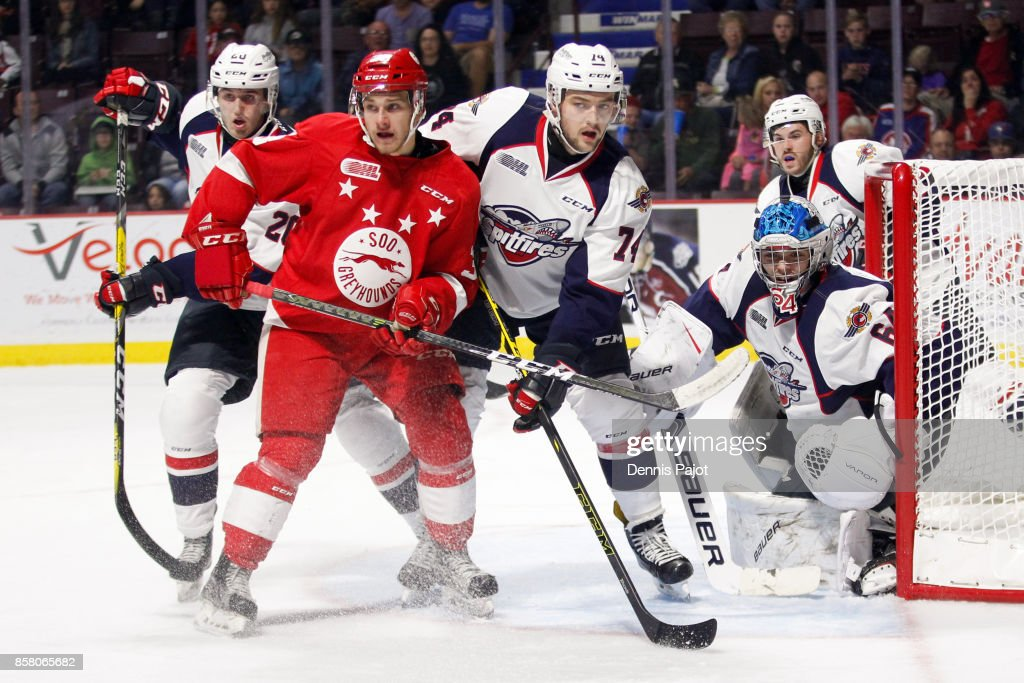 Forward Hayden Verbeek #38 of the Sault Ste. Marie Greyhounds battles in front of the net against defenceman Sean Day #74 and Michael DiPietro #64 of the Windsor Spitfires on October 5, 2017 at the WFCU Centre in Windsor, Ontario, Canada.