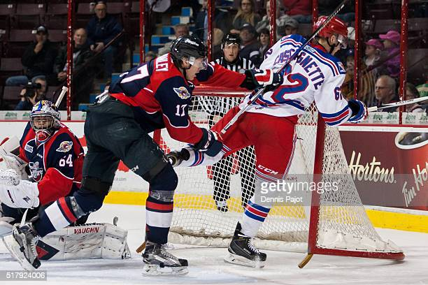 Forward Jacob Cascagnette of the Kitchener Rangers is checked into the net by defenceman Logan Stanley of the Windsor Spitfires during game 3 of the...