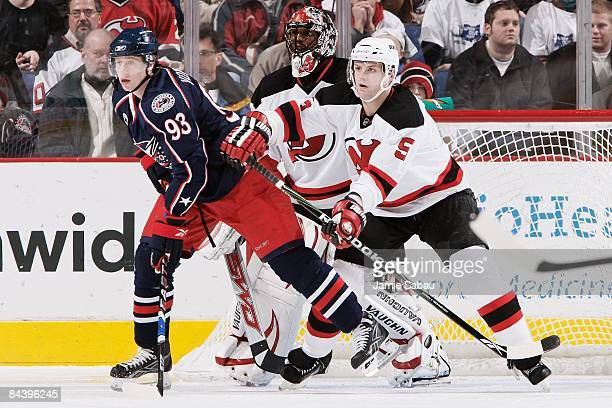 Forward Jakub Voracek of the Columbus Blue Jackets and defenseman Colin White of the New Jersey Devils battle for position in front of goaltender...