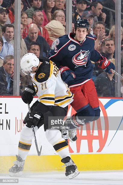 Forward Jared Boll of the Columbus Blue Jackets leaps to avoid a check by forward P.J. Axelsson of the Boston Bruins on March 10, 2009 at Nationwide...