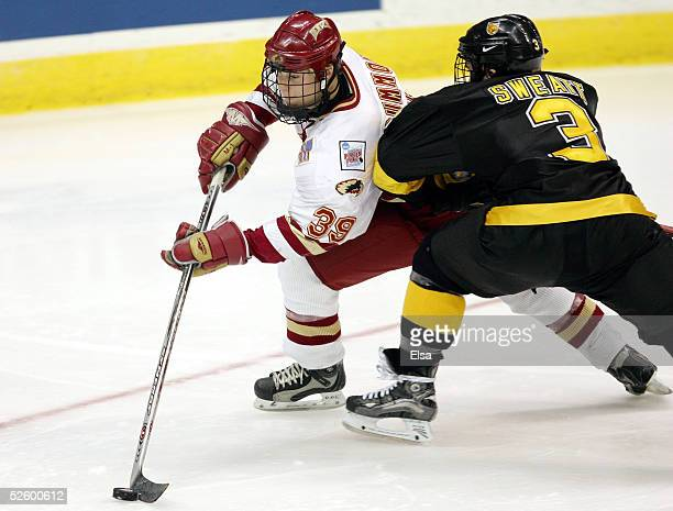 Forward Jeff Drummond of the Denver Pioneers tries to get around defenseman Lee Sweatt of the Colorado College Tigers on April 7, 2005 during the...