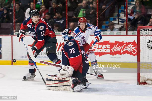 Forward Jeremy Bracco of the Kitchener Rangers battles for a rebound in front of the net against goaltender Mario Culina of the Windsor Spitfires on...