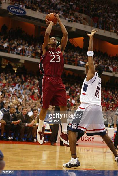 Forward Jermaine Dearman of the Southern Illinois Salukis shoots over forward Mike Hayes of the University of Connecticut Huskies during the 2002...