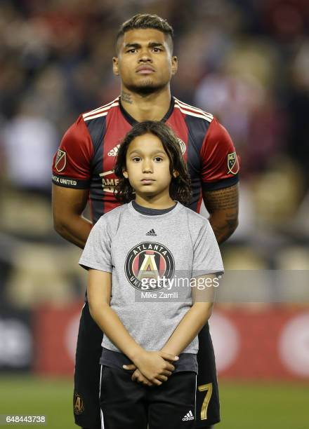 Forward Josef Martinez of Atlanta United stands with a young fan for the national anthem before the game against the New York Red Bulls at Bobby Dodd...