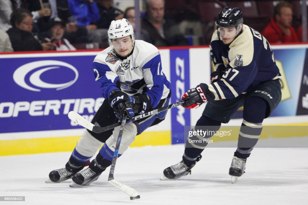 Forward Julien Gauthier #12 of the Saint John Sea Dogs moves the puck against forward Graham Knott #37 of the Windsor Spitfires on May 19, 2017 during Game 1 of the Mastercard Memorial Cup at the WFCU Centre in Windsor, Ontario, Canada.