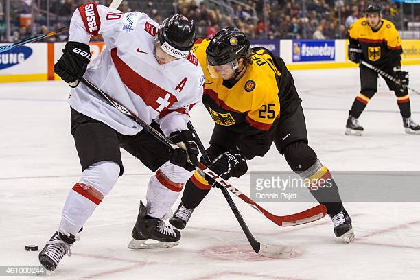 Forward Kevin Fiala of Switzerland battles for the puck against forward Fabio Pfohl of Germany during the 2015 IIHF World Junior Championship on...