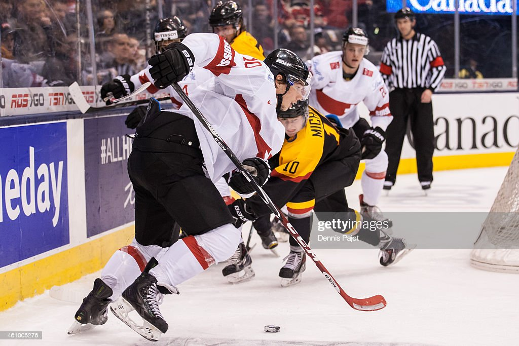 Forward Kevin Fiala #10 of Switzerland moves the puck against forward Marc Michaelis #10 of Germany during the 2015 IIHF World Junior Championship on January 03, 2015 at the Air Canada Centre in Toronto, Ontario, Canada.