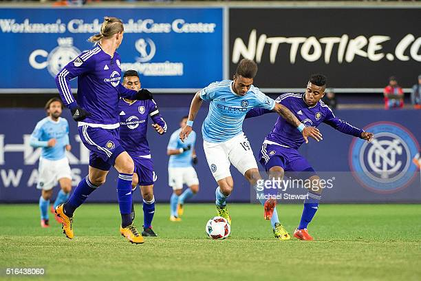 Forward Khiry Shelton of New York City FC tries to push the ball past Orlando City SC players Brek Shea and Seb Hines during the Orlando City SC vs...