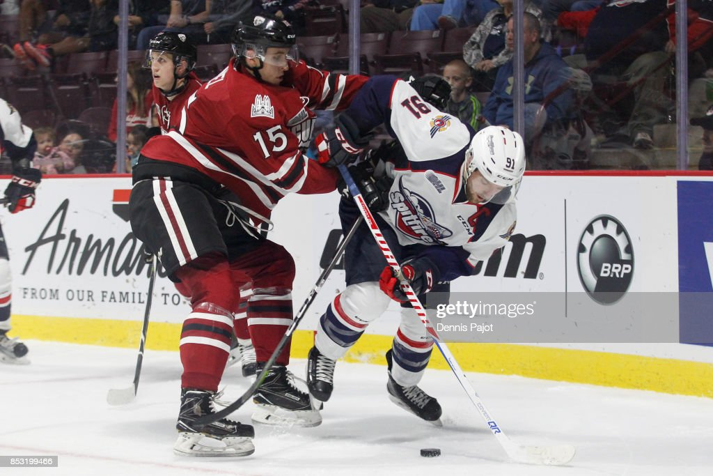 Forward Liam Hawell #15 of the Guelph Storm battles for the puck against forward Aaron Luchuk #91 of the Windsor Spitfires on September 24, 2017 at the WFCU Centre in Windsor, Ontario, Canada.