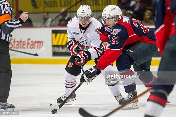 Forward Logan Brown of the Windsor Spitfires battles for the puck on a faceoff against Mikkel Aagaard of the Niagara Ice Dogs on February 15 2015 at...