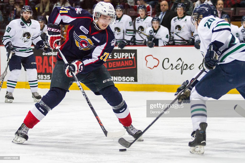 Forward Logan Brown #21 of the Windsor Spitfires moves the puck against defenceman Josh Wesley #20 of the Plymouth Whalers on February 18, 2015 at the WFCU Centre in Windsor, Ontario, Canada.