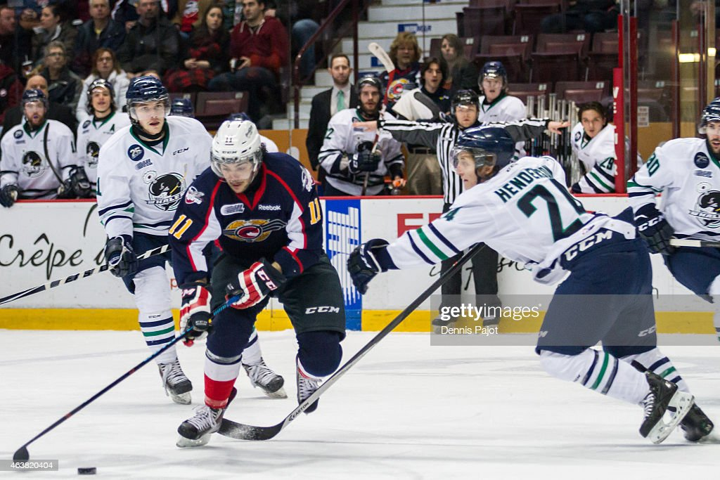 Forward Lucas Venuto #11 of the Windsor Spitfires moves the puck against defenceman Mathieu Henderson #24 of the Plymouth Whalers on February 18, 2015 at the WFCU Centre in Windsor, Ontario, Canada.