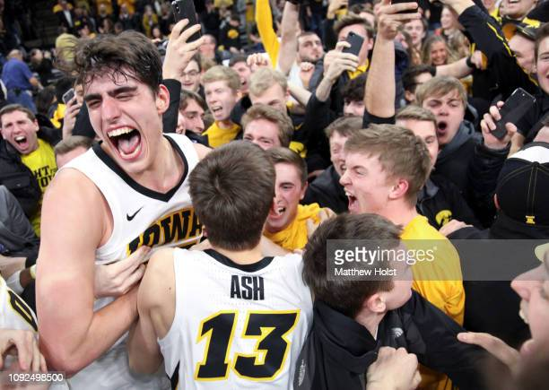 Forward Luka Garza and guard Austin Ash of the Iowa Hawkeyes celebrates with fans after the upset over the Michigan Wolverines on February 1 2019 at...