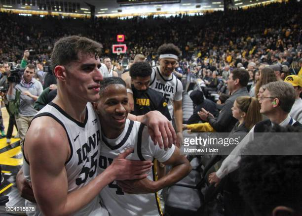 Forward Luka Garza and guard Bakari Evelyn of the Iowa Hawkeyes walk off the court following their match-up against the Penn State Nittany Lions at...
