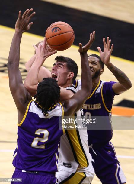 Forward Luka Garza of the Iowa Hawkeyes drives in the first half between forward Cameron Burrell and guard Tamell Pearson of the Western Illinois...