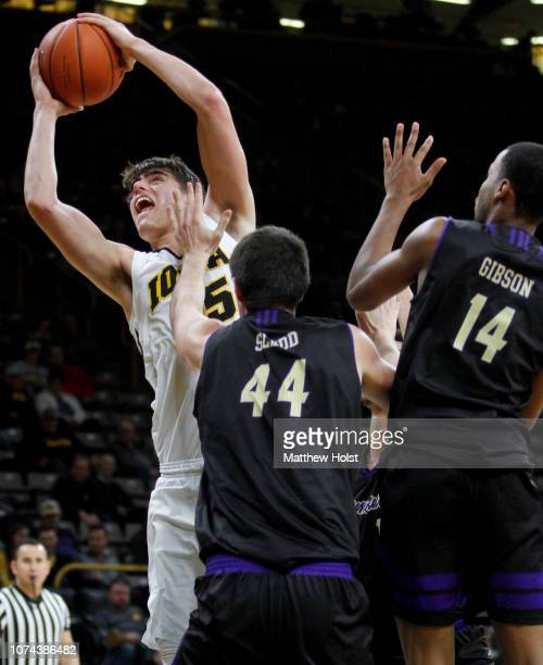 Forward Luka Garza of the Iowa Hawkeyes takes a shot in the second half in front of forward Adam Sledd and guard Kameron Gibson of the Western...