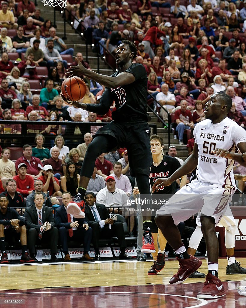 Forward Mangok Mathiang #12 of the Louisville Cardinals drive pass Center Michael Ojo #50 of the Florida State Seminoles at the Donald L. Tucker Center on January 21, 2017 in Tallahassee, Florida. The 10th ranked Seminoles defeated the 12th ranked Cardinals 73 to 68.