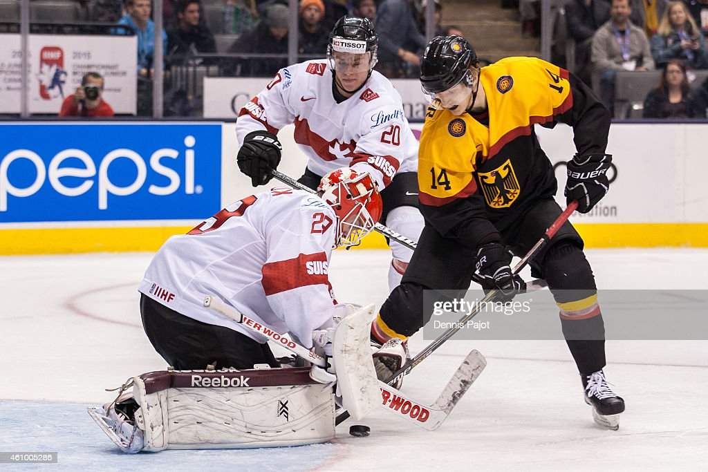 Forward Manuel Wiederer #14 of Germany battles for a rebound against goaltender Gauthier Descloux #29 of Switzerland during the 2015 IIHF World Junior Championship on January 03, 2015 at the Air Canada Centre in Toronto, Ontario, Canada.