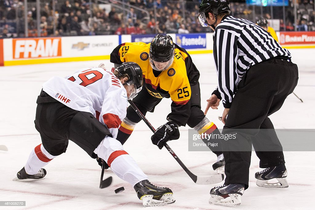 Forward Marc Aeschlimann #19 of Switzerland battles for the puck on a faceoff against forward Fabio Pfohl #25 of Germany during the 2015 IIHF World Junior Championship on January 03, 2015 at the Air Canada Centre in Toronto, Ontario, Canada.