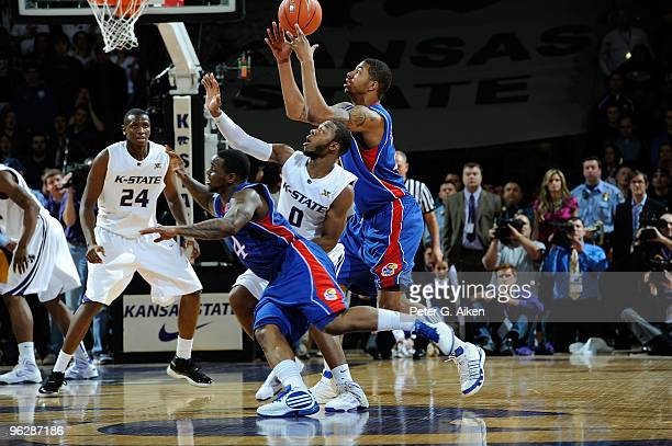 Forward Marcus Morris of the Kansas Jayhawks reaches for a loose ball with guard Jacob Pullen of the Kansas State Wildcats and teammate Sherron...