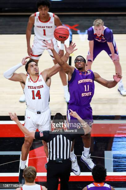 Forward Marcus Santos-Silva of the Texas Tech Red Raiders and forward Jamaure Gregg of the Northwestern State Demons jump for the tip-off during the...